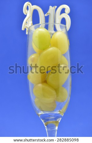Fresh green grapes in glass with 2016 new year celebration on blue background - stock photo