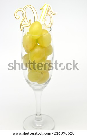 Fresh green grapes in glass with 2015 new year celebration on white background - stock photo