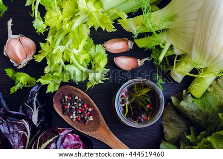 Fresh green ingredients for vegetable salad, olive oil and spices over wooden table background. Healthy eating. Vegetables background. Healthy food. Food flat lay. Top view.  - stock photo