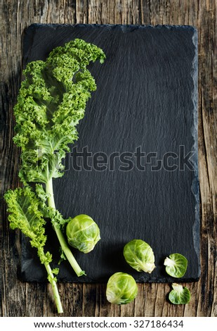 Fresh Green Kale and Brussels sprouts on wooden background with copy space - stock photo