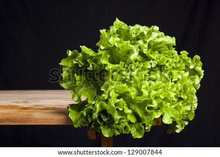 fresh green lettuce on wooden table on black background - stock photo
