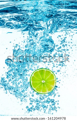 Fresh green lime in the clear water on white background. - stock photo