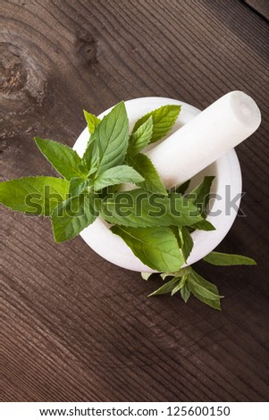 Fresh green mint in mortar on wood background closeup - stock photo