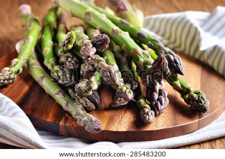 Fresh green organic asparagus sprouts on a cutting board on a wooden table ready for cooking. Healthy food - stock photo