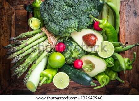 Fresh green organic vegetables on rustic dark wood background.Vegan food concept. - stock photo