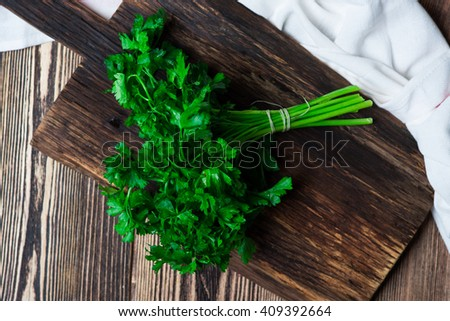 Fresh green parsley on wooden cutting board over dark wooden background - stock photo