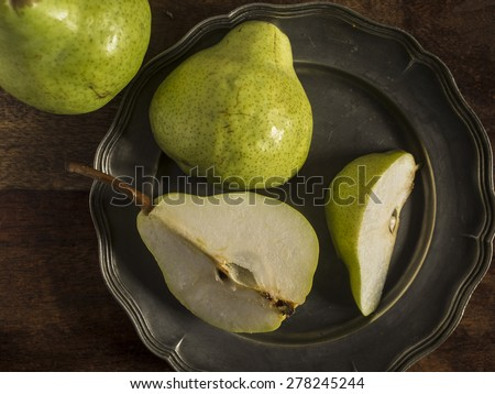 Fresh green pears on a distressed wooden table. One of the pears has been sliced and placed on a pewter plate. - stock photo
