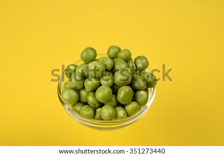 Fresh green peas in bowl isolated on yellow background