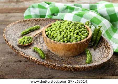 Fresh green peas in bowl on wooden table, closeup - stock photo