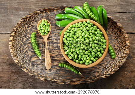 Fresh green peas in bowl on wooden tray, top view - stock photo