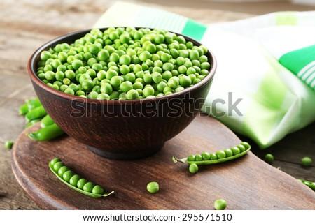Fresh green peas in clay bowl on wooden cutting board, closeup - stock photo