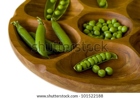 Fresh green peas in wooden bowl - stock photo