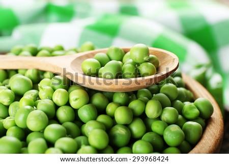 Fresh green peas in wooden bowl, closeup - stock photo