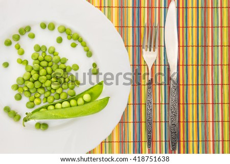 Fresh green peas on plate with fork and knife closeup, on colorful bamboo placemat - stock photo