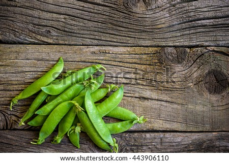 fresh green peas over a natural wood table, placed in a nice way. tasty, good for background. - stock photo