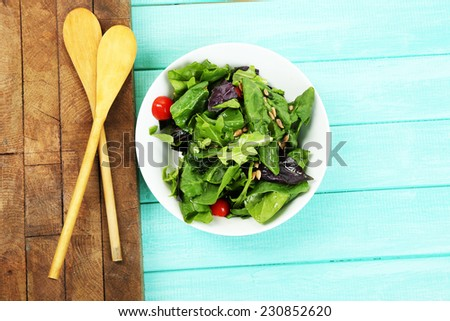 Fresh green salad in bowl on wooden table - stock photo