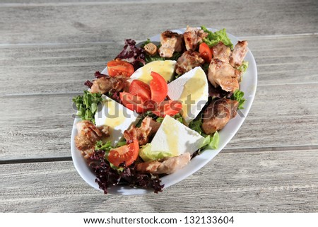 fresh green salad with chicken and cheese on top served on a plate