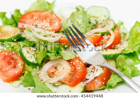 Fresh green salad with cucumber, tomato, onion, lettuce, sesame, oil, soy sauce, oil and dry spices. Low aperture shot, selective focus - stock photo