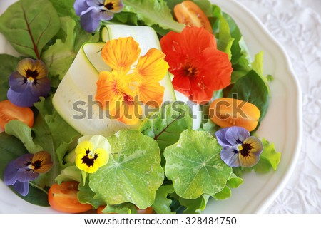 Fresh green salad with edible flowers in white serving dish - stock photo