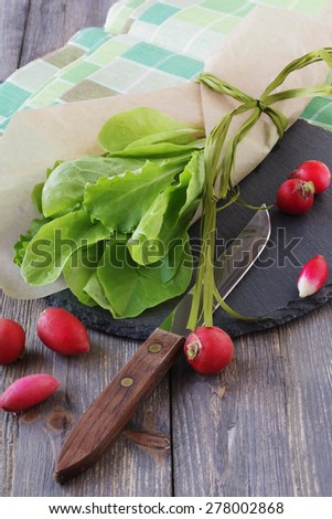 Fresh green salad with red radishes on an old wooden table background. Selective focus. - stock photo