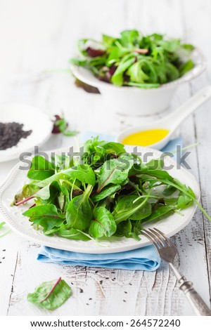 Fresh green salad with spinach, arugula, romaine and lettuce and sesame seeds on a rustic white background, selective focus - stock photo