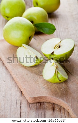 fresh green sliced apples on wooden board - stock photo