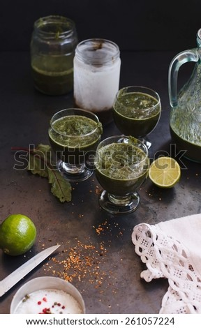 Fresh green smoothie in glass jars with lime taken on dark metal surface. Natural, fresh and vegetarian juice and drink concept. Rustic style. - stock photo