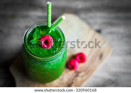 Fresh green smoothie on rustic wooden background - stock photo