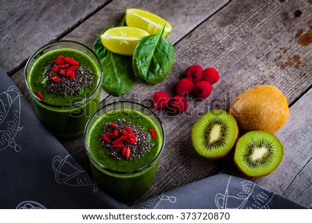 Fresh green smoothie sprinkled with chia seeds and goji berries in the background fruits and vegetables on wooden table.  - stock photo