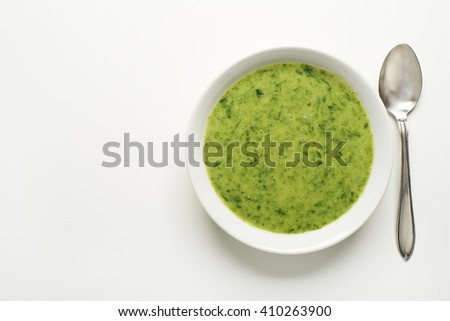 Fresh green soup on white background overhead shoot. - stock photo