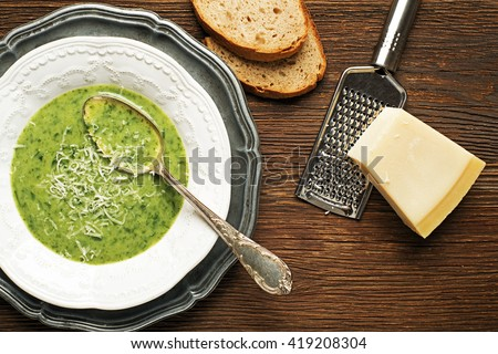 Fresh green soup on wooden background overhead shoot. - stock photo