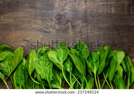 fresh green spinach on vintage wooden texture,top view - stock photo