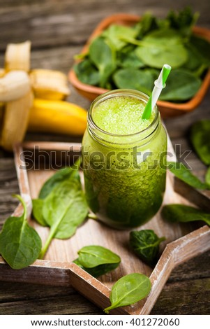 Fresh green spinach smoothie on wooden table - stock photo