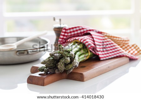 Fresh green spring asparagus on a wooden cut board on a kitchen table ready to cook or to eat. Closeup, horizontal - stock photo