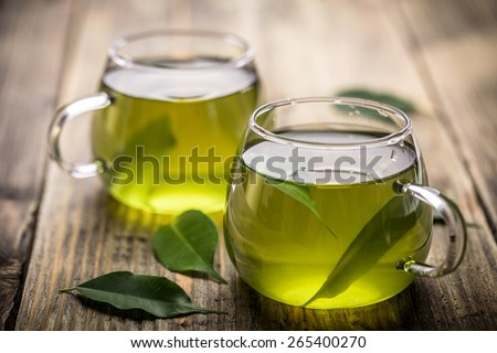 Fresh green tea with tea leaves in the water - stock photo