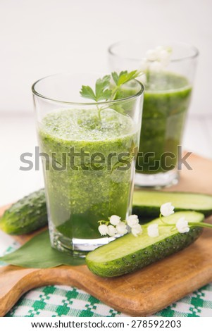fresh green vegetable smoothie in transparent glass in a studio