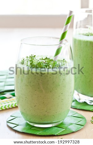 Fresh Green vegetable smoothie in two glasses with cress