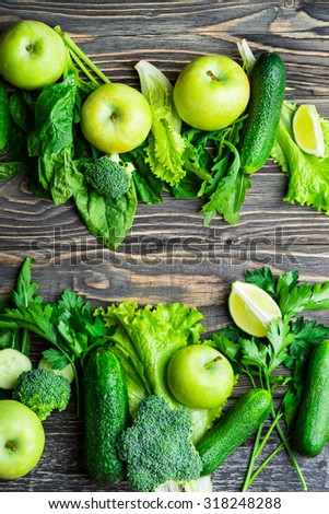 Fresh green vegetables and fruits on vintage wooden background. Detox, diet or healthy food concept