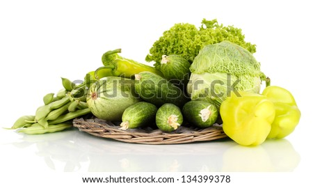 fresh green vegetables on wicker mat isolated on white