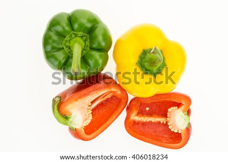 Fresh green, yellow and cut in two red bell peppers, isolated on white background. - stock photo