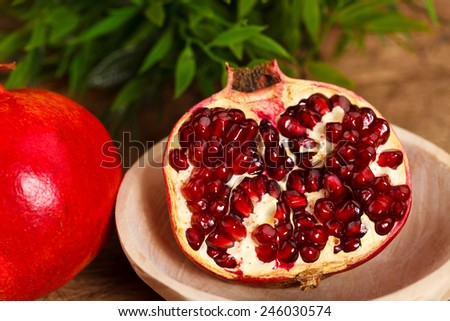 Fresh grenadine in wooden plate, green leaves on the back - stock photo