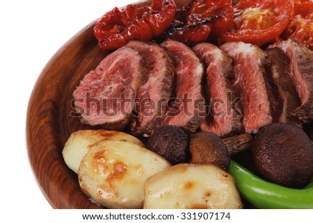 fresh grilled bbq beef meat rib eye steak on wooden plate with baked tomatoes mushroom, potatoes, hot chili pepper isolated on white background empty space for text - stock photo