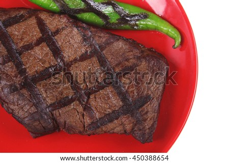 fresh grilled bbq roast beef steak on red plate with green chili pepper isolated on white background - stock photo