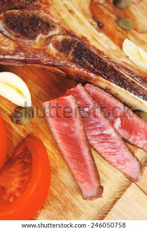 fresh grilled beef meat fillet sliced on wooden board with tomatoes and red pepper and cutlery isolated  over white background - stock photo