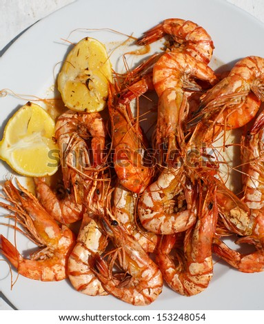 Fresh grilled black tiger prawns on white plate with lemon - stock photo