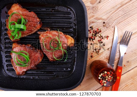fresh grilled bloody beef steaks on black grill plate on wood