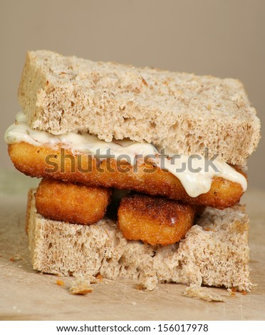 fresh grilled fish fingers with tartar sauce on a sandwich of wholemeal bread - stock photo