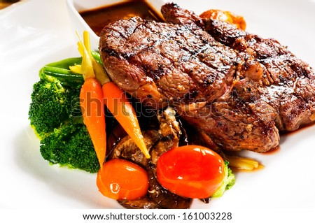 fresh grilled ribeye steak with broccoli,carrot and cherry tomatoes on side