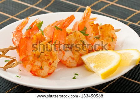 Fresh grilled shrimps with lemon on white plate - stock photo