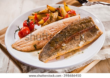 Fresh grilled trout or salmon fillets with a serving of healthy roasted vegetables on a white plate for a gourmet seafood dinner - stock photo